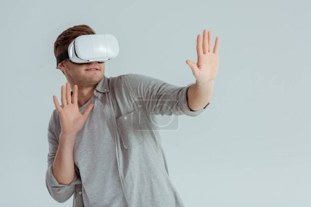 Photo for Surprised man gesturing while wearing virtual reality headset isolated on grey - Royalty Free Image