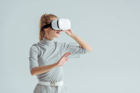 Photo for Girl in grey clothing and vr headset touching air while having virtual reality experience isolated on grey - Royalty Free Image