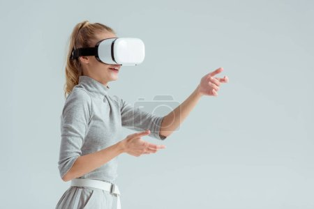 Photo for Surprised woman gesturing while having virtual reality experience isolated on grey - Royalty Free Image