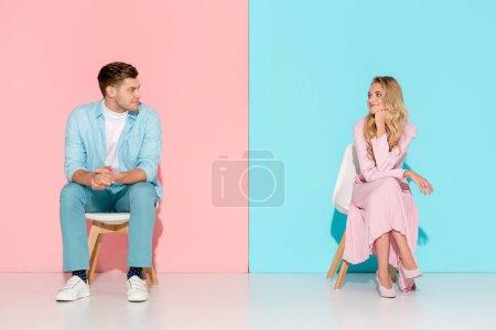 Foto de Hombre con los brazos cruzados sentados en la silla y mirando a mujer aburre tocar barbilla sobre fondo rosa y azul - Imagen libre de derechos