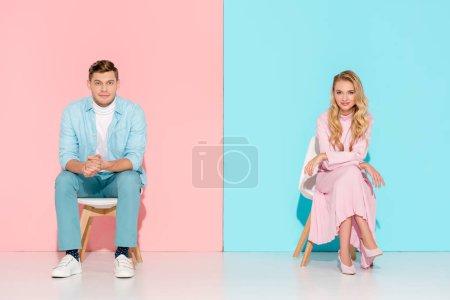 Foto de Pareja con los brazos cruzados, sentado en una silla y mirando a cámara sobre fondo rosa y azul - Imagen libre de derechos