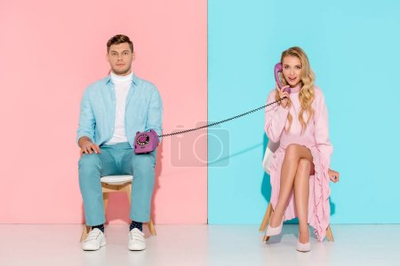 Photo for Woman having conversation while bored man holding purple vintage telephone on pink and blue background - Royalty Free Image