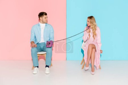 smiling woman having conversation while man holding purple vintage telephone on pink and blue background