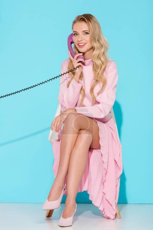 Photo for Beautiful woman with legs crossed talking on vintage telephone with turquoise background - Royalty Free Image