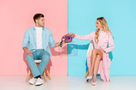 Photo for Couple sitting on chairs and holding purple vintage telephone on pink and blue background - Royalty Free Image