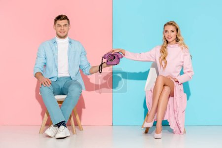 beautiful couple sitting on chairs and holding purple vintage telephone on pink and blue background
