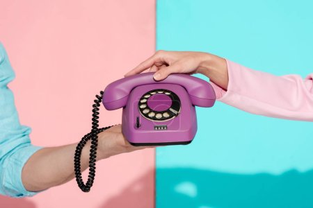 Photo for Cropped view of man and woman holding purple vintage telephone on pink and blue background - Royalty Free Image