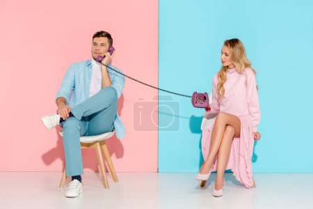 Photo for Dissatisfied woman holding purple vintage telephone while man talking with pink and blue background - Royalty Free Image