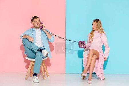 Photo pour Femme insatisfaite tenant purple téléphone vintage tout en souriant homme parler avec fond rose et bleu - image libre de droit