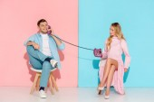 dissatisfied woman holding purple vintage telephone while smiling man talking with pink and blue background