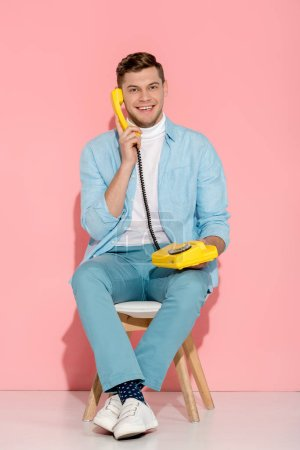smiling man sitting and talking on yellow vintage telephone with pink background