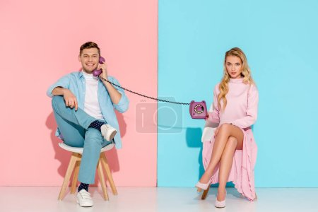 Photo for Dissatisfied woman holding purple vintage telephone while handsome man talking on pink and blue background - Royalty Free Image