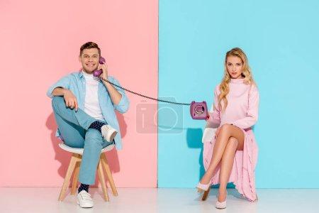 Photo pour Femme insatisfaite tenant purple téléphone vintage tout en bel homme parlant sur fond rose et bleu - image libre de droit