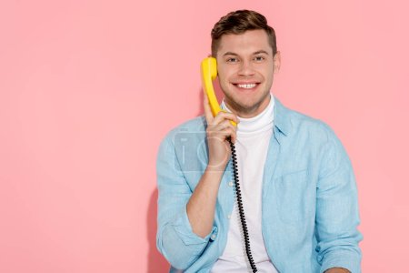 Photo for Man talking on yellow vintage telephone with pink background - Royalty Free Image