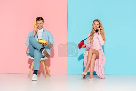 Photo for Beautiful couple sitting and having conversation on vintage telephones with pink and blue background - Royalty Free Image