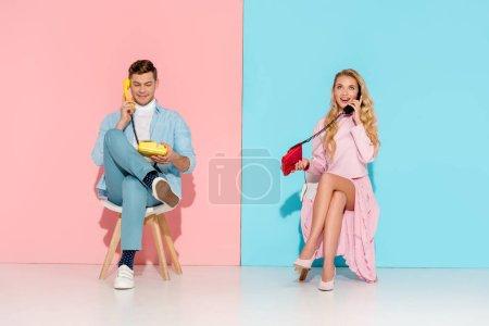 Photo pour Beau couple assis et avoir la conversation sur les téléphones vintage avec fond rose et bleu - image libre de droit