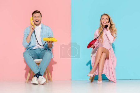 excited couple sitting and having conversation on vintage telephones with pink and blue background