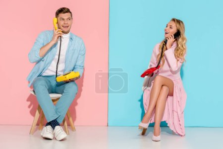 Photo for Happy couple sitting and having conversation on vintage telephones with pink and blue background - Royalty Free Image
