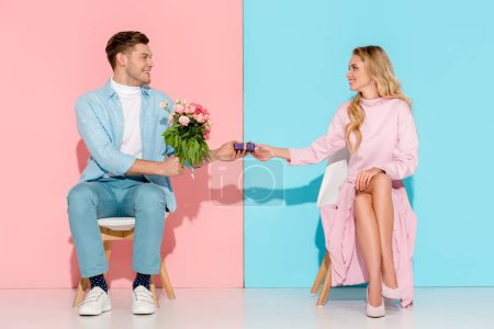 beautiful couple sitting on chairs while man presenting gift box with flower bouquet to woman on pink and blue background