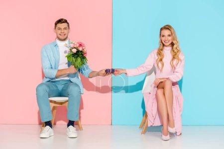 Photo pour Couple assis sur des chaises tandis que l'homme présente boîte-cadeau avec bouquet de fleurs à la femme souriante sur fond rose et bleu - image libre de droit