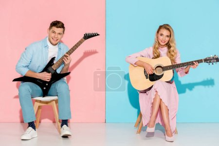 couple sitting on chairs, playing electric and acoustic guitars and looking at camera on pink and blue background