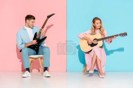 Photo for Beautiful couple playing electric and acoustic guitars on pink and blue background - Royalty Free Image