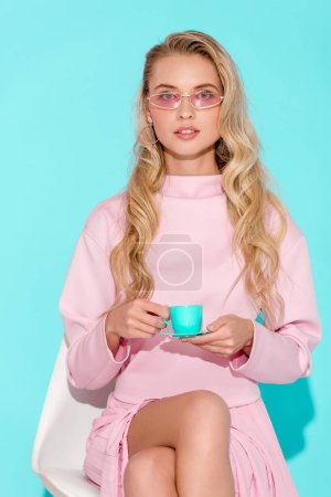 Photo for Beautiful woman in pink outfit and sunglasses holding toy coffee cup and looking at camera on turquoise background - Royalty Free Image