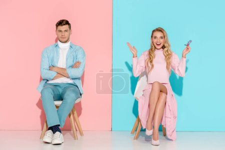 Photo for Man with arms crossed and excited woman with hands in air sitting on chairs on pink and blue background - Royalty Free Image