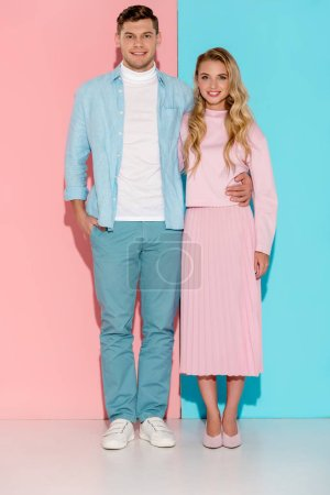 smiling couple looking at camera and posing on pink and blue background