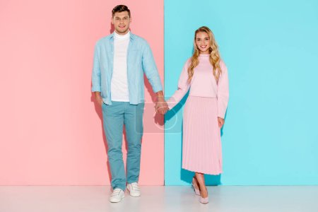 beautiful couple holding hands and looking at camera on pink and blue background