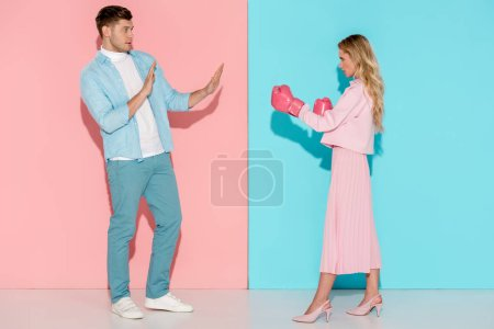 scared man gesturing with hands near aggressive woman in pink boxing gloves on pink and blue background