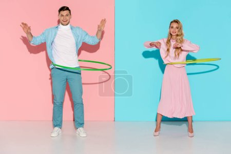 beautiful couple looking at camera and exercising with hula hoops on pink and blue background