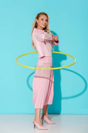 beautiful woman in pink clothing looking at camera and exercising with hula hoop on turquoise background