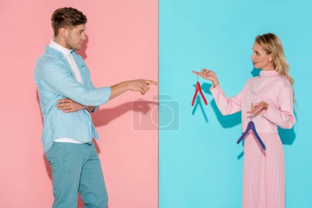 Photo for Handsome man pointing with finger at woman and choosing empty clothes hangers on pink and blue background - Royalty Free Image