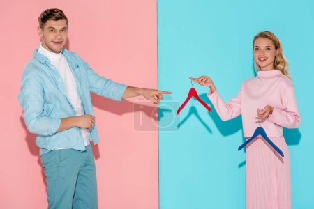 Photo for Smiling man pointing with finger at woman and choosing empty clothes hangers on pink and blue background - Royalty Free Image