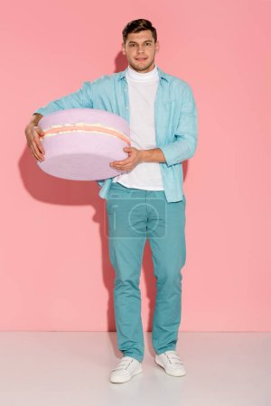 man in blue clothing holding big macaroon model and looking at camera on pink background