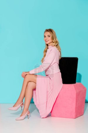 smiling woman in pink dress sitting on big nail polish model, posing and looking at camera on turquoise background