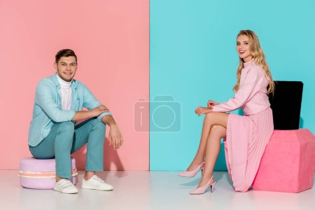 Photo for Couple sitting on big macaroon and nail polish models while looking at camera on pink and blue background - Royalty Free Image