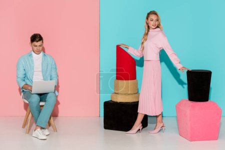 beautiful woman posing with nail polish and lipstick models while man sitting on chair and using laptop on pink and blue background