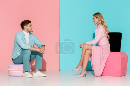 Photo for Couple sitting on big macaroon and nail polish models on pink and blue background - Royalty Free Image