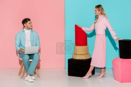 woman posing with nail polish and lipstick models while man sitting on chair and using laptop on pink and blue background