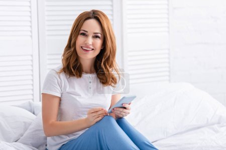 Photo for Happy attractive woman holding smartphone and looking at camera in bed on weekend - Royalty Free Image