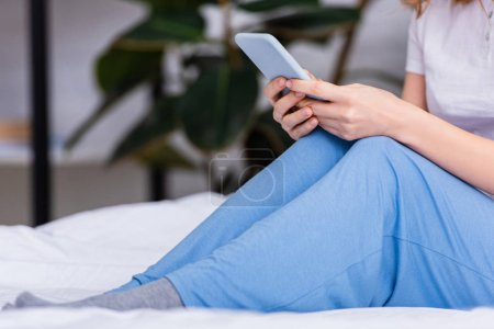 cropped image of woman resting in bed and using smartphone at home on weekend