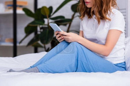 cropped image of woman with ginger hair resting in bed and using smartphone at home on weekend