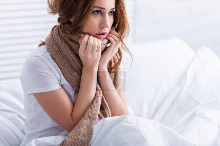 Photo pour Femme malade avec écharpe assis sur le lit à la maison et regardant loin - image libre de droit