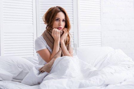 Photo pour Femme malade touchant écharpe sur le cou et assis sur le lit à la maison - image libre de droit