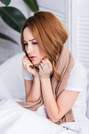 sick redhair woman with scarf sitting on bed at home