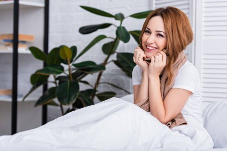 smiling sick woman with scarf sitting on bed at home and looking at camera