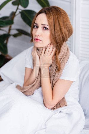 sick woman touching painful neck with scarf and sitting on bed at home and looking at camera