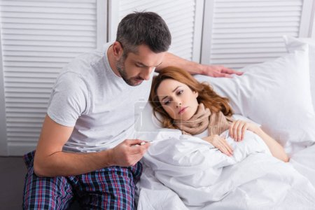 husband checking temperature of sick wife and looking at thermometer in bedroom